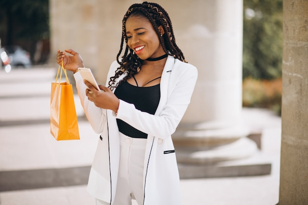 African woman with yellow shopping bags Free Photo