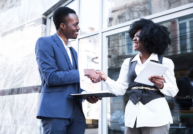An african young businessman and businesswoman shaking hands Free Photo