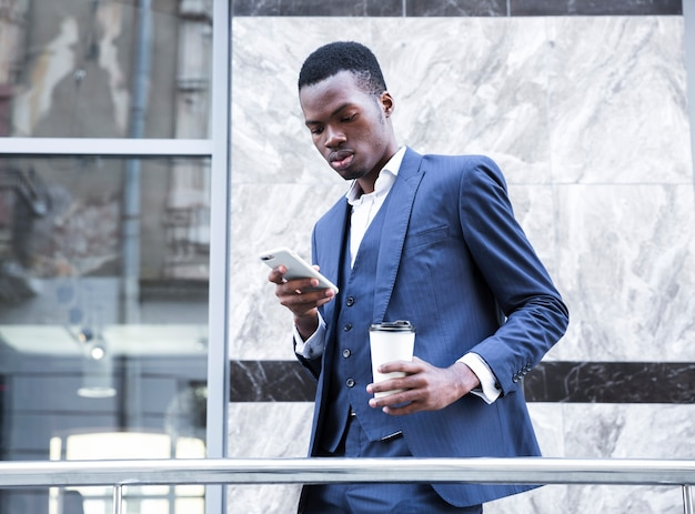 An african young businessman holding disposable coffee cup using mobile phone Free Photo
