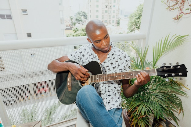 African young man playing the guitar sitting in the balcony Free Photo