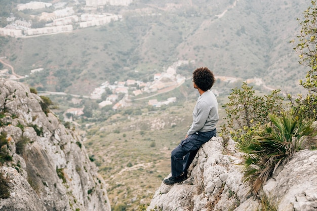 An african young man sitting on rock overlooking the mountain view Free Photo