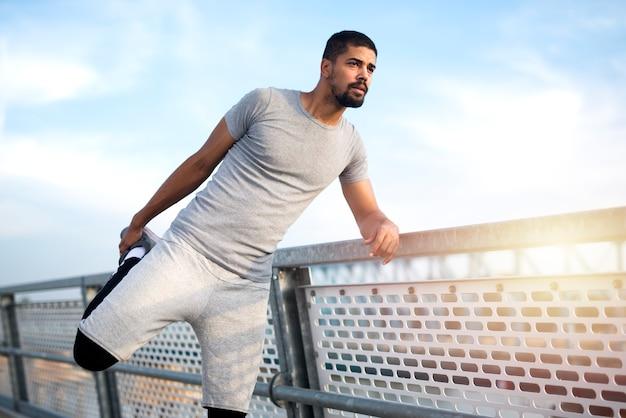 Atleta afroamericano che allunga le gambe prima di correre Foto Gratuite