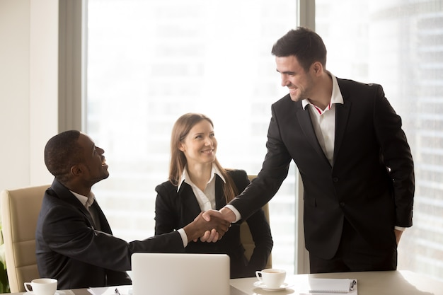 Afro american and caucasian cheerful businessmen handshaking at Free Photo