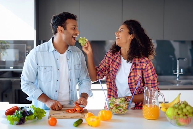 Afro american couple cooking salad on kitchen. Premium Photo