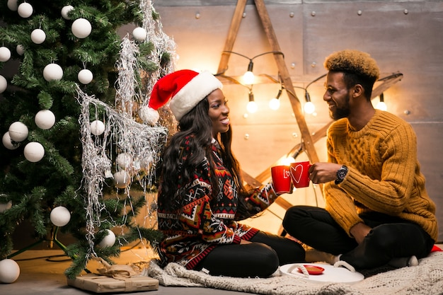 Afro American Couple Drinking Coffee By The Christmas Tree Photo