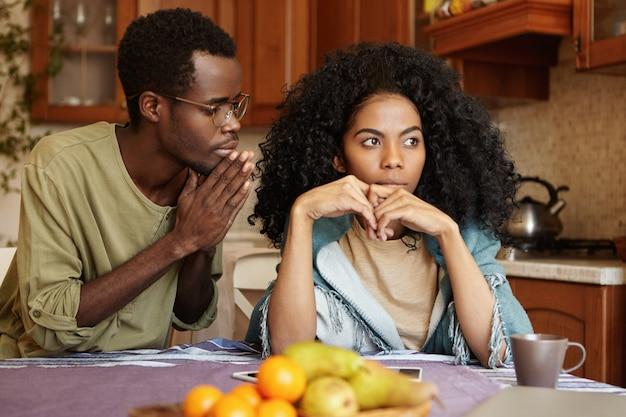Афроамериканская пара переживает не лучшие времена в своих отношениях. виновный неверный молодой человек, держась за руки, умоляет свою злую жену простить его за измену, пытаясь сладко поболтать с ней Бесплатные Фотографии
