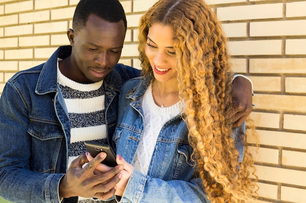 Afro american couple looking at smartphone Free Photo