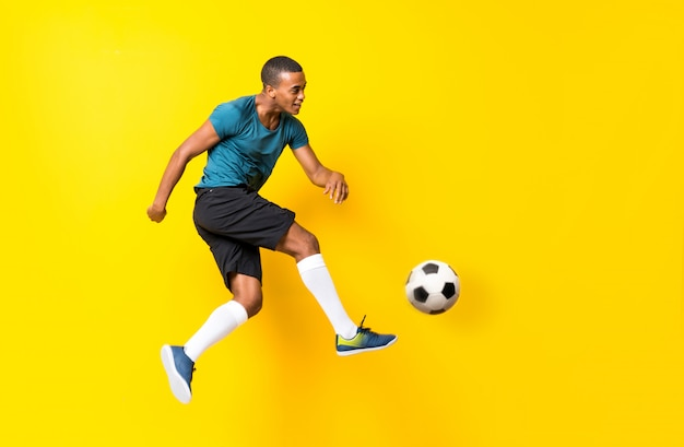 Afro american football player man over isolated yellow Premium Photo