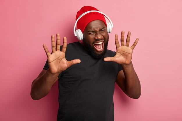 Il ragazzo afroamericano tiene i palmi in avanti, apre ampiamente la bocca, indossa un cappello rosso e una maglietta nera, esclama di gioia, si gode la musica in cuffia Foto Gratuite