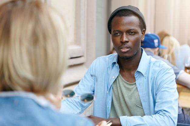 シャツと黒い帽子をかぶった黒い肌のアフロアメリカンの男が女友達の前に座って、お互いに話し合って、ニュースについて話し合っています。カフェで会う取引先 無料写真
