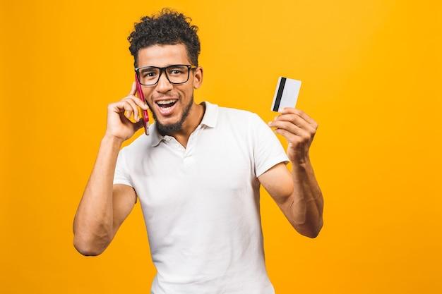 アフロアメリカンの男は服を着て、携帯電話を使用して、プラスチック製のクレジットカードを表示します。 Premium写真