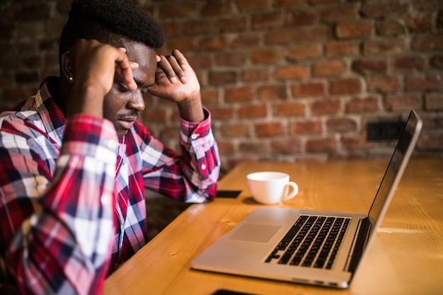 Afro american man feeling headache while doing distance work in coffee shop tired with failure of plans, male entrepreneur overworked solving problems with startup project exhausted with hard schedule Free Photo
