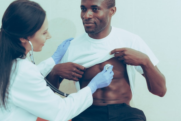 Afro-american man on reception at female doctor Premium Photo