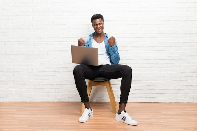 Afro american man working with his laptop celebrating a victory Premium Photo