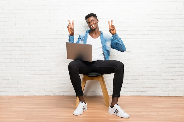 Afro american man working with his laptop smiling and showing victory sign Premium Photo