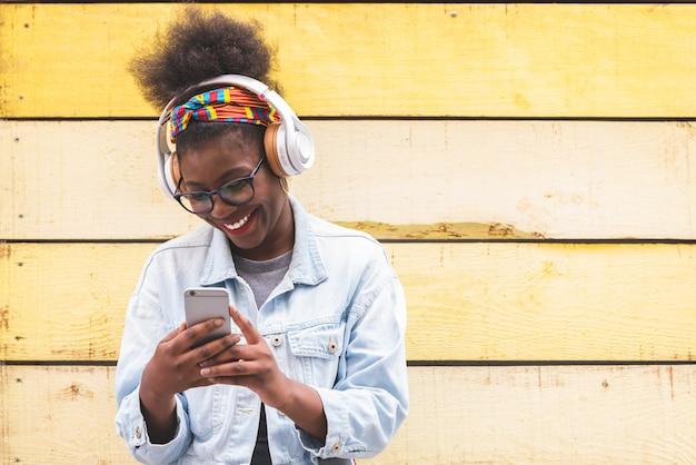 Afro american teenage girl using mobile phone outdoors. Premium Photo