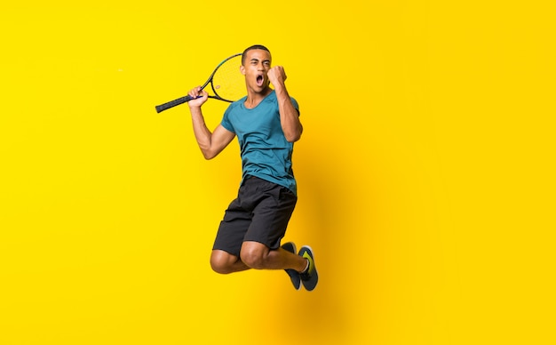 Afro american tennis player man over isolated yellow Premium Photo