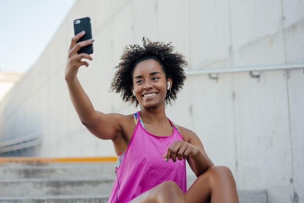 携帯電話で自分撮りをし、屋外で運動した後にリラックスするアフロアスリート女性 無料写真