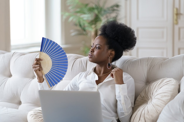 Afro business woman suffering from heat stroke sitting in living room at home using waving fan Premium Photo
