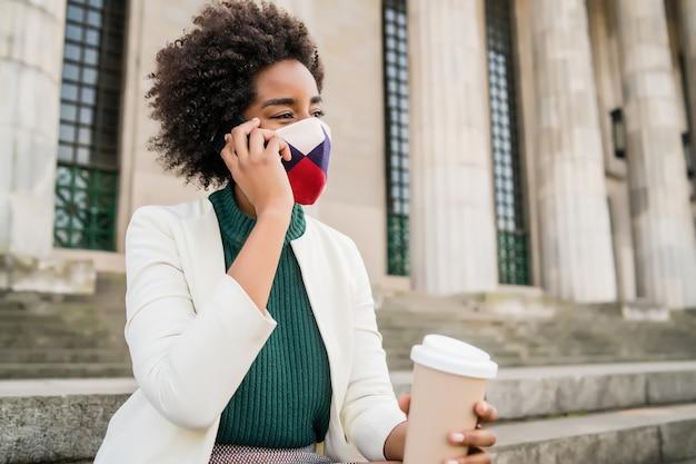 通りの屋外の階段に座って保護マスクを着用し、電話で話しているアフロビジネスウーマン。ビジネスと都市のコンセプト。 無料写真