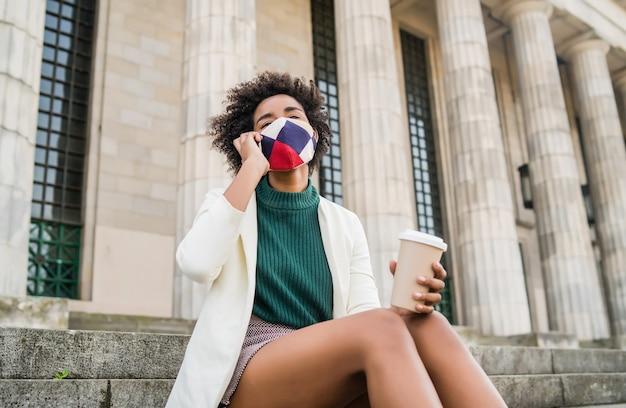 防毒マスクを着用し、通りの屋外の階段に座って電話で話しているアフロビジネスウーマン。ビジネスと都市のコンセプト。 無料写真