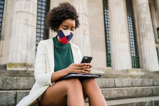通りの屋外の階段に座っている間、保護マスクを着用し、彼女の携帯電話を使用してアフロビジネス女性。ビジネスと都市のコンセプト。 無料写真