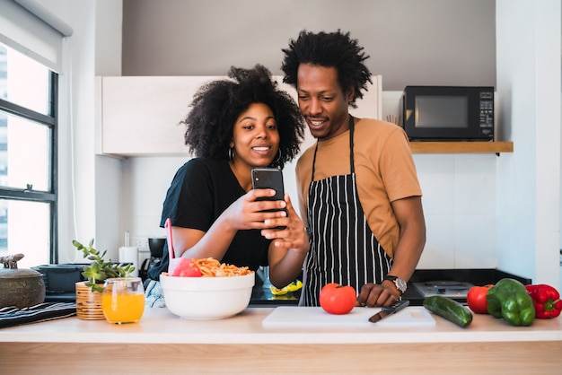 Afro couple cooking together and using phone at home. Premium Photo