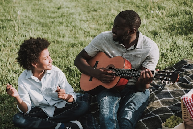Afro father play on guitar and looking on son in picnic. Premium Photo