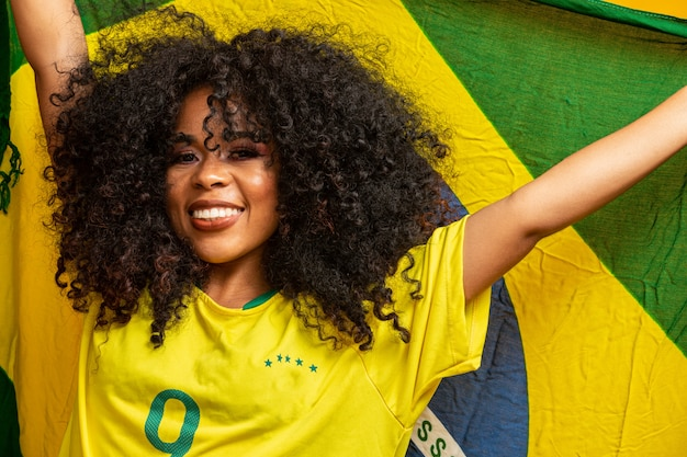 Afro girl cheering for favorite brazilian team, holding national flag in yellow wall. Premium Photo