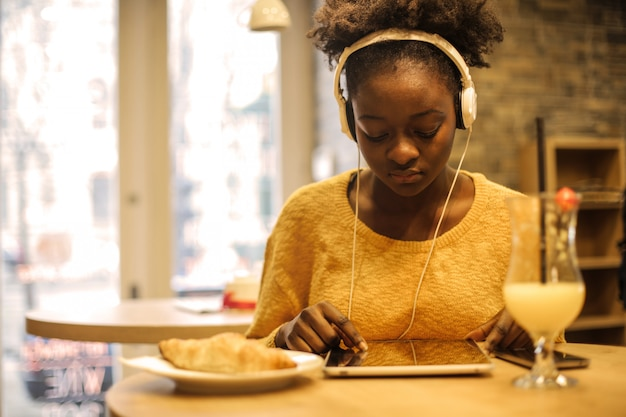 Afro girl using a tablet in a bistro Premium Photo