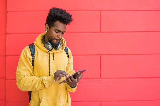 Афро человек, используя свой цифровой планшет с наушниками Premium Фотографии