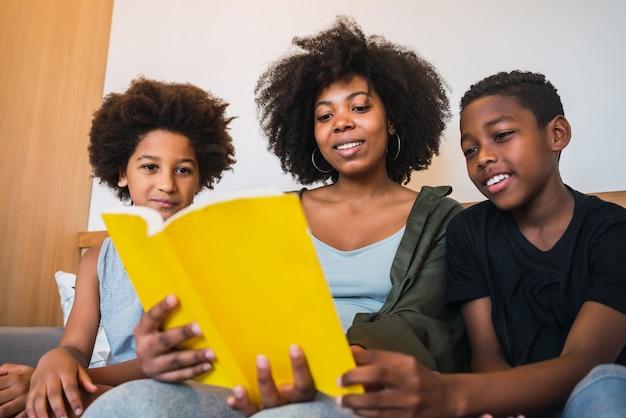 子供たちに本を読んでいるアフロの母。 無料写真