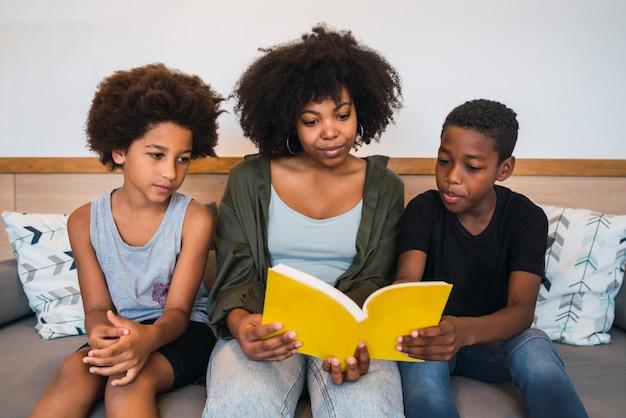 アフロの母親が子供たちに本を読んでいます。 Premium写真