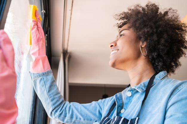 自宅でぼろきれでウィンドウをクリーニングするアフロの女性。 無料写真