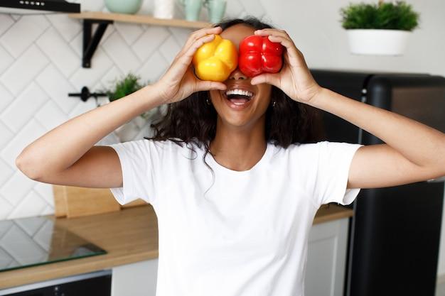 La gioia afro della donna tiene due peperoni Foto Gratuite