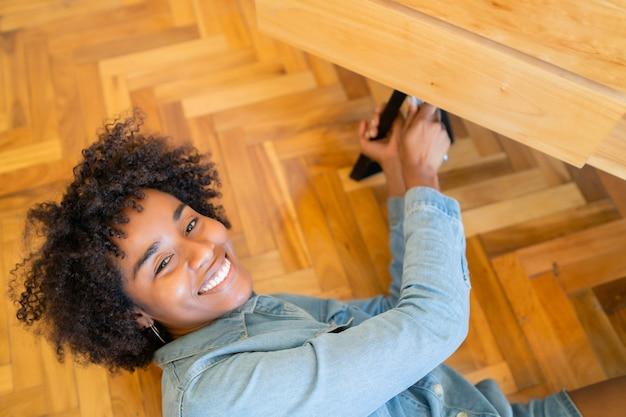 Donna di afro che ripara mobilia a casa. Foto Gratuite