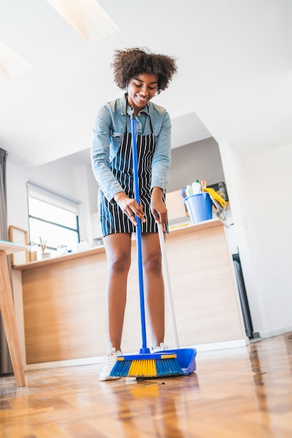 premium photo afro woman sweeping floor with broom at home https www freepik com profile preagreement getstarted 7575112