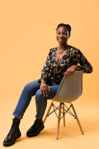 Afroamerican model sitting on chair Free Photo