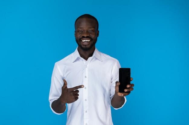 ひげを生やしたafroamerican男は白いシャツで携帯電話を見せています。 無料写真