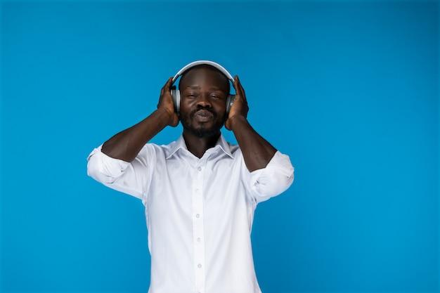 目を閉じてひげを生やしたafroamerican男は白いシャツで大きなヘッドフォンで 無料写真