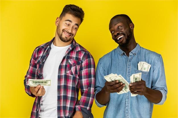 Afroamericanの男は非公式の服でヨーロッパの男とお金を共有していて、両方とも楽しそうに笑っている 無料写真