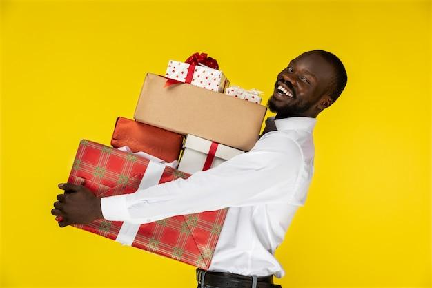 たくさんのプレゼントでひげを生やした若いafroamerican男を笑ってください。 無料写真