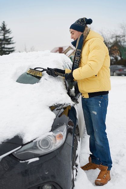 Dopo una grande bufera di neve, l'auto deve essere pulita dalla neve Foto Gratuite