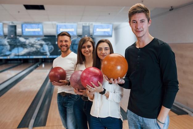 Dopo la partita. i giovani amici allegri si divertono al bowling durante i fine settimana Foto Gratuite