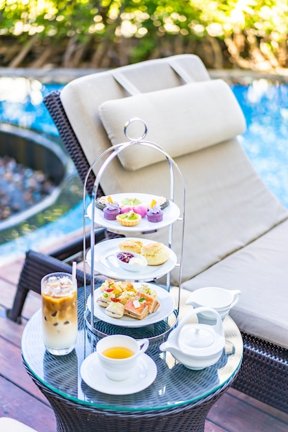 Afternoon tea set with latte coffee and hot tea on table near chair around swimming pool Free Photo