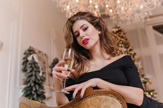 Contro alberi di natale decorati, su una sedia costosa, appoggiata allo schienale, seduta giovane e attraente donna di 25 anni, con un bicchiere di champagne tra le mani e con sguardo appassionato Foto Gratuite