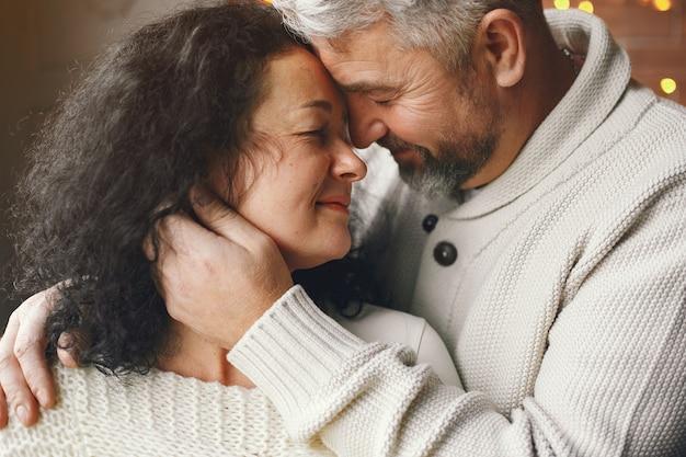 Возраст и концепция людей. старшие пары с подарочной коробкой на фоне огней. женщина в белом трикотажном комбинезоне. Бесплатные Фотографии