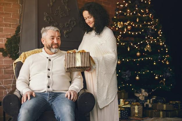 年齢と人の概念。ライトの背景にギフトボックスと年配のカップル。白いニットのセーターを着た女性。 無料写真