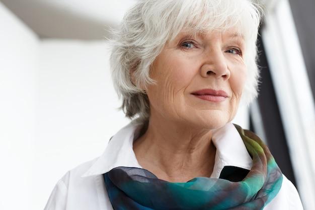 Возраст, зрелость, красота, стиль и концепция моды. крупным планом изображение стильной стильной пожилой пожилой женщины с морщинами, седыми волосами и естественным макияжем, проводящей свободное время в помещении, улыбаясь Бесплатные Фотографии