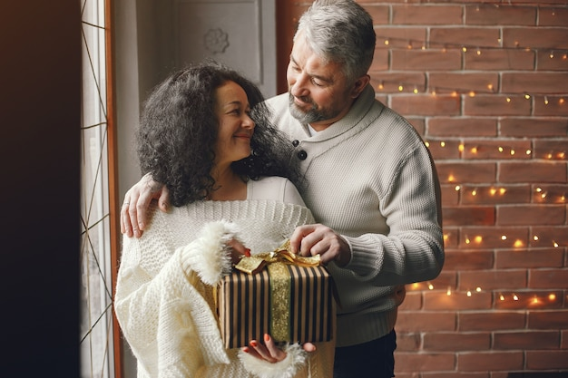 Age and people concept . senior couple with gift box over lights background. woman in a white knited sweatre. Free Photo